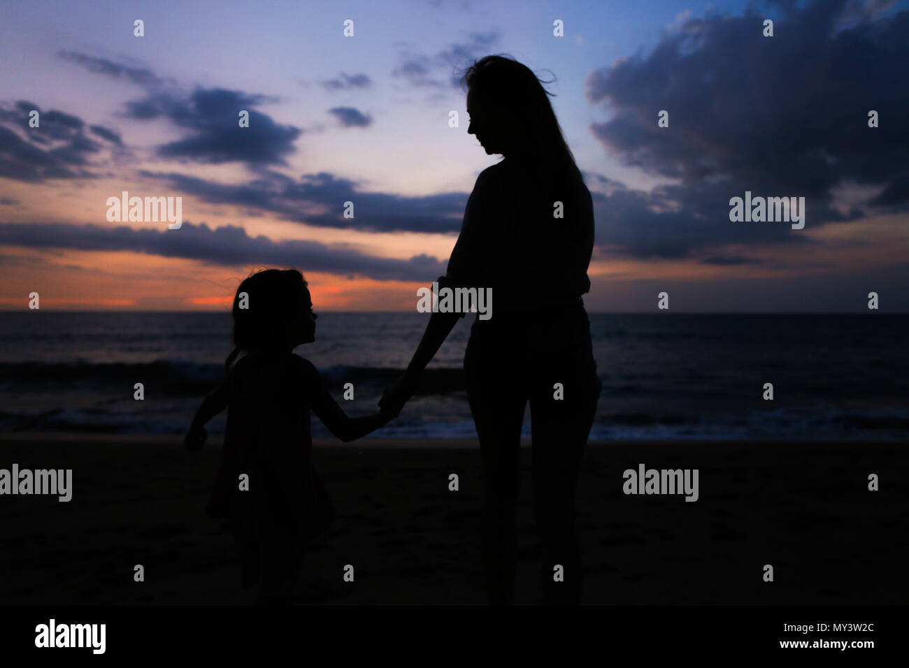 7a30c482def6 Black silhouette of young female person walking with little girl near sea  in sunset background.