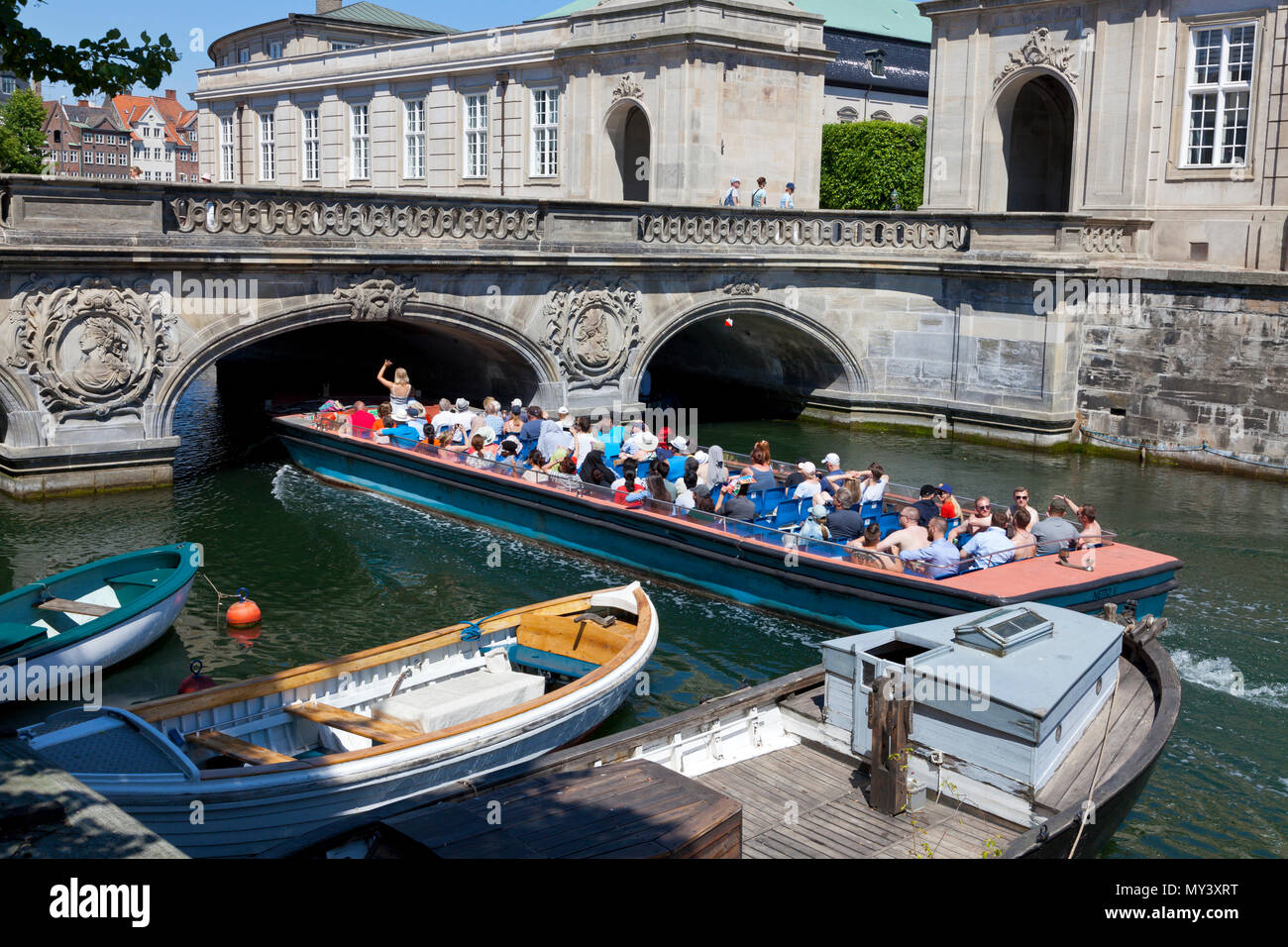Canal cruise boat full of tourists passing the historic Marble Bridge, Marmorbroen, entrance to the Riding Ground at Christiansborg Castle, Copenhagen - Stock Image