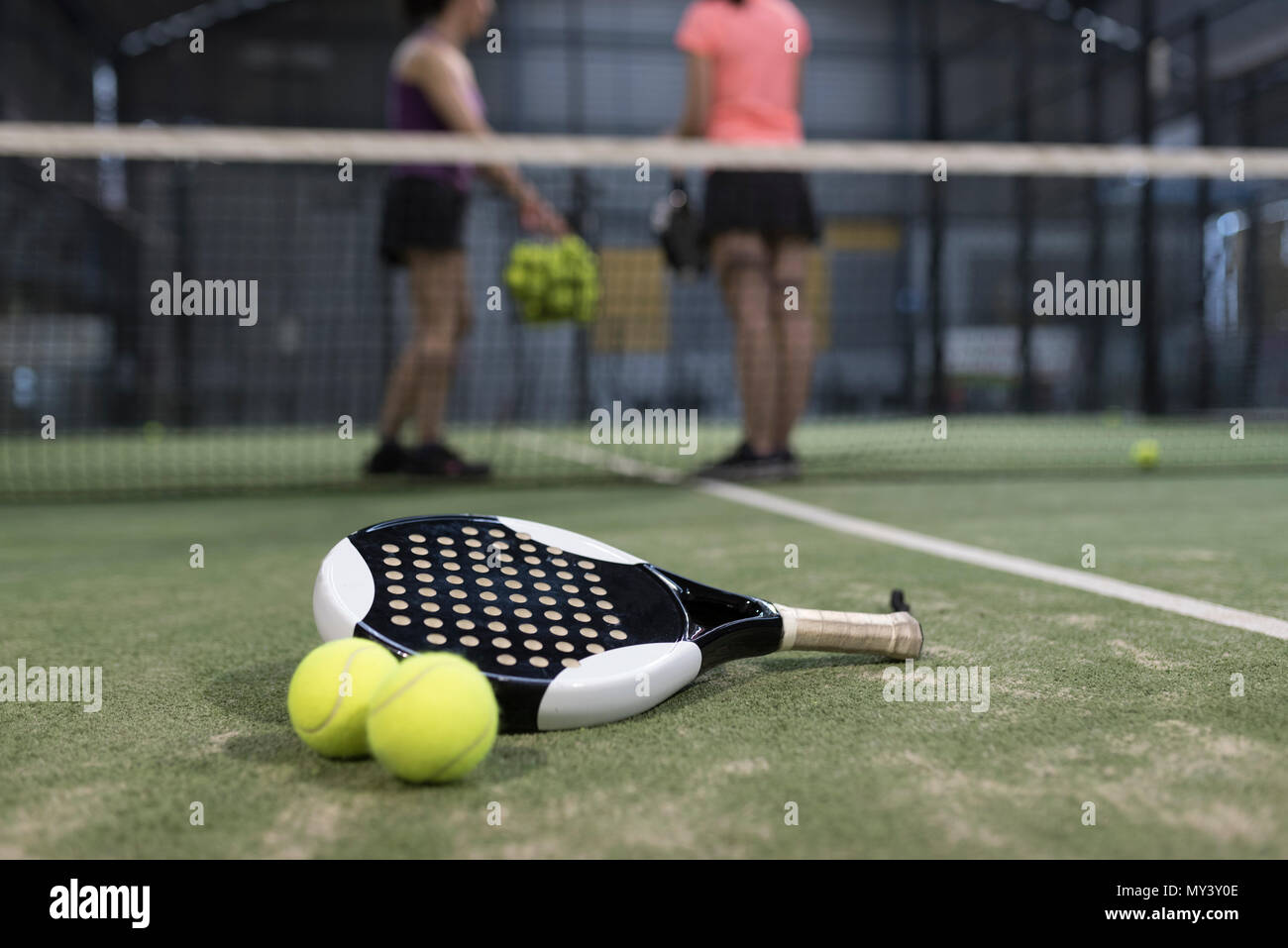 Paddle tennis objects on turf ready for tournament and women in background Stock Photo