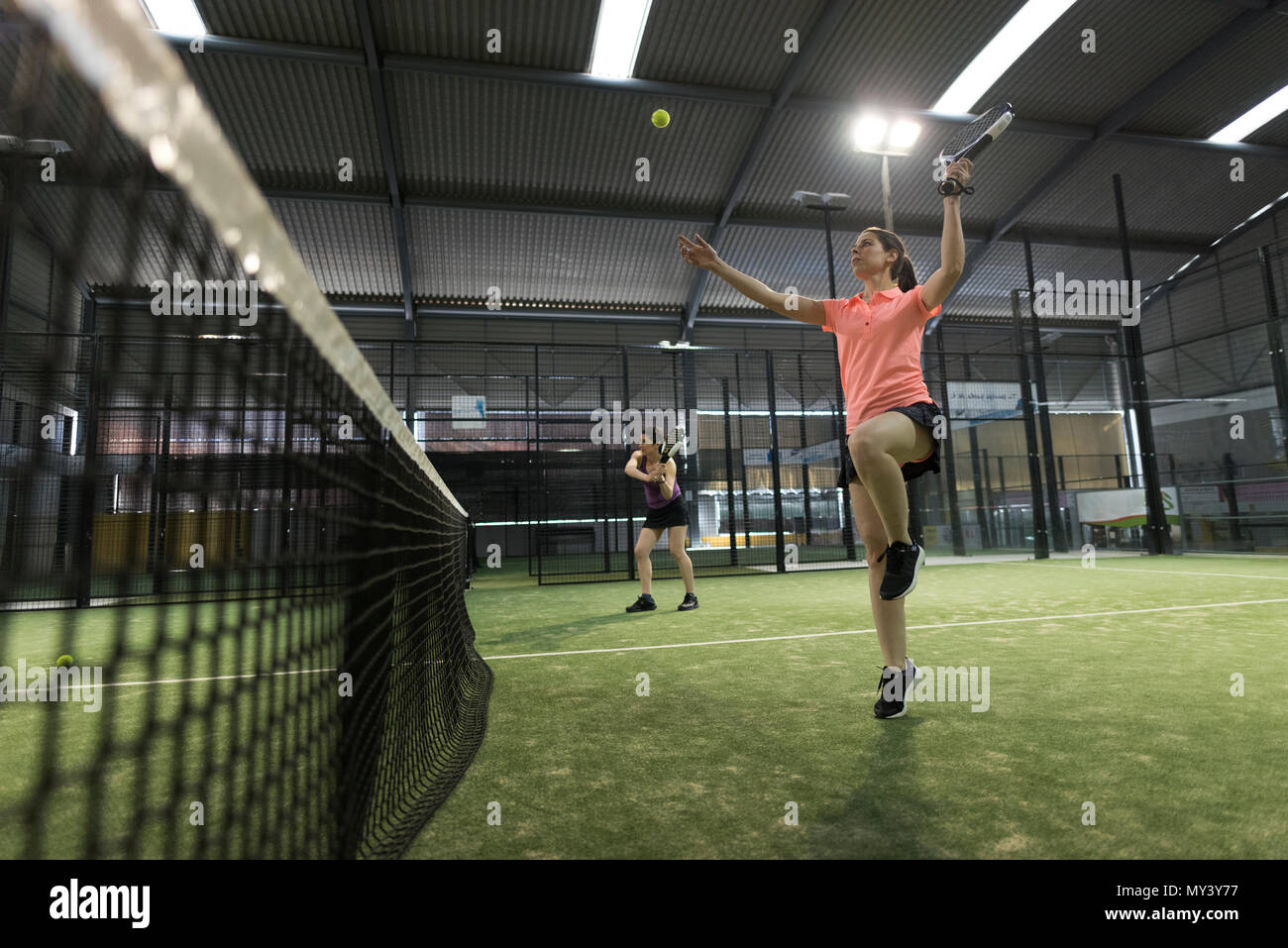 Paddle tennis player woman smashing ball in match while jumping - Stock Image