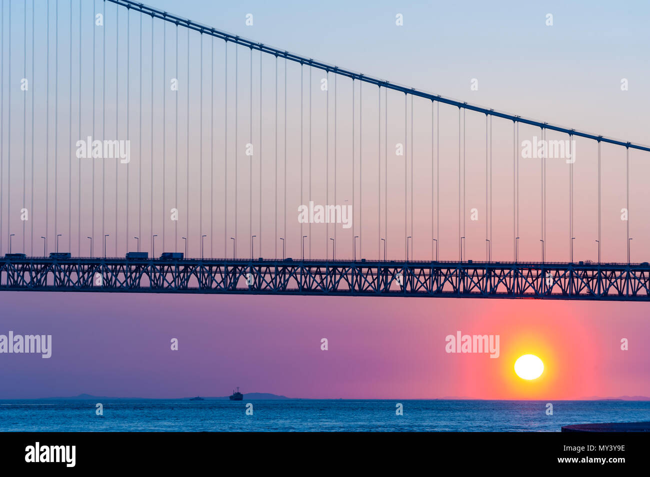 sunset with Akashi Kaikyo bridge on twilight sky at Kobe port, Japan - Stock Image