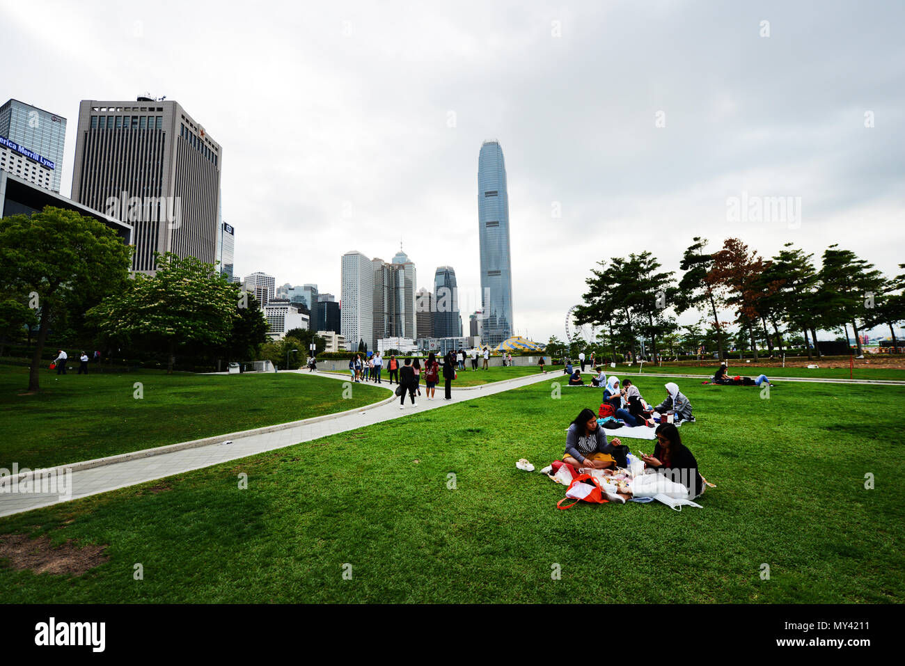 Filipina domestic helpers enjoying their Sunday day off in Tamar park in Hong Kong. - Stock Image