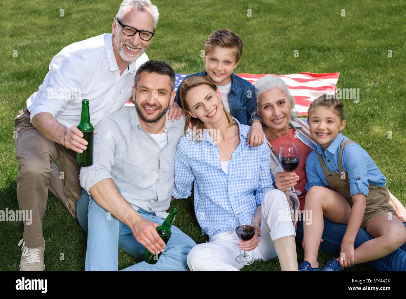 Happy family of three generations sitting together on green lawn and smiling at camera - Stock Image