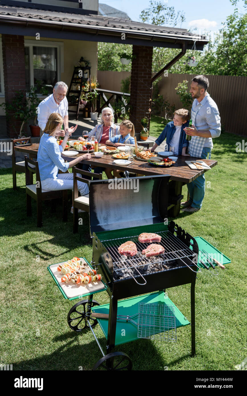 Happy family of three generations eating and drinking at table while grilling meat outdoors - Stock Image