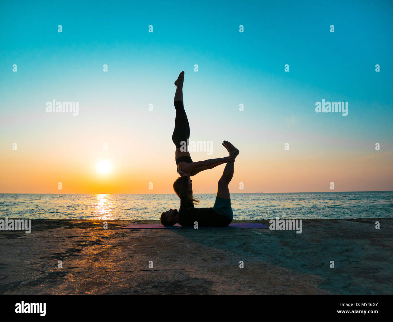 Young beautiful couple practicing acro yoga on the sea beach near water. Man and woman doing everyday practice outdoor on nature background. Healthy l Stock Photo