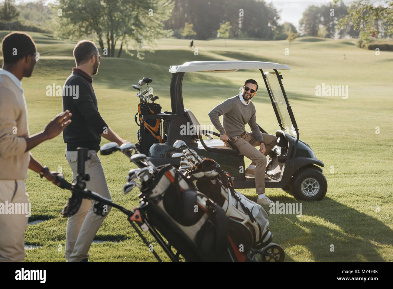multiethnic friends with golf bags and golf cart spending time together on golf course - Stock Image