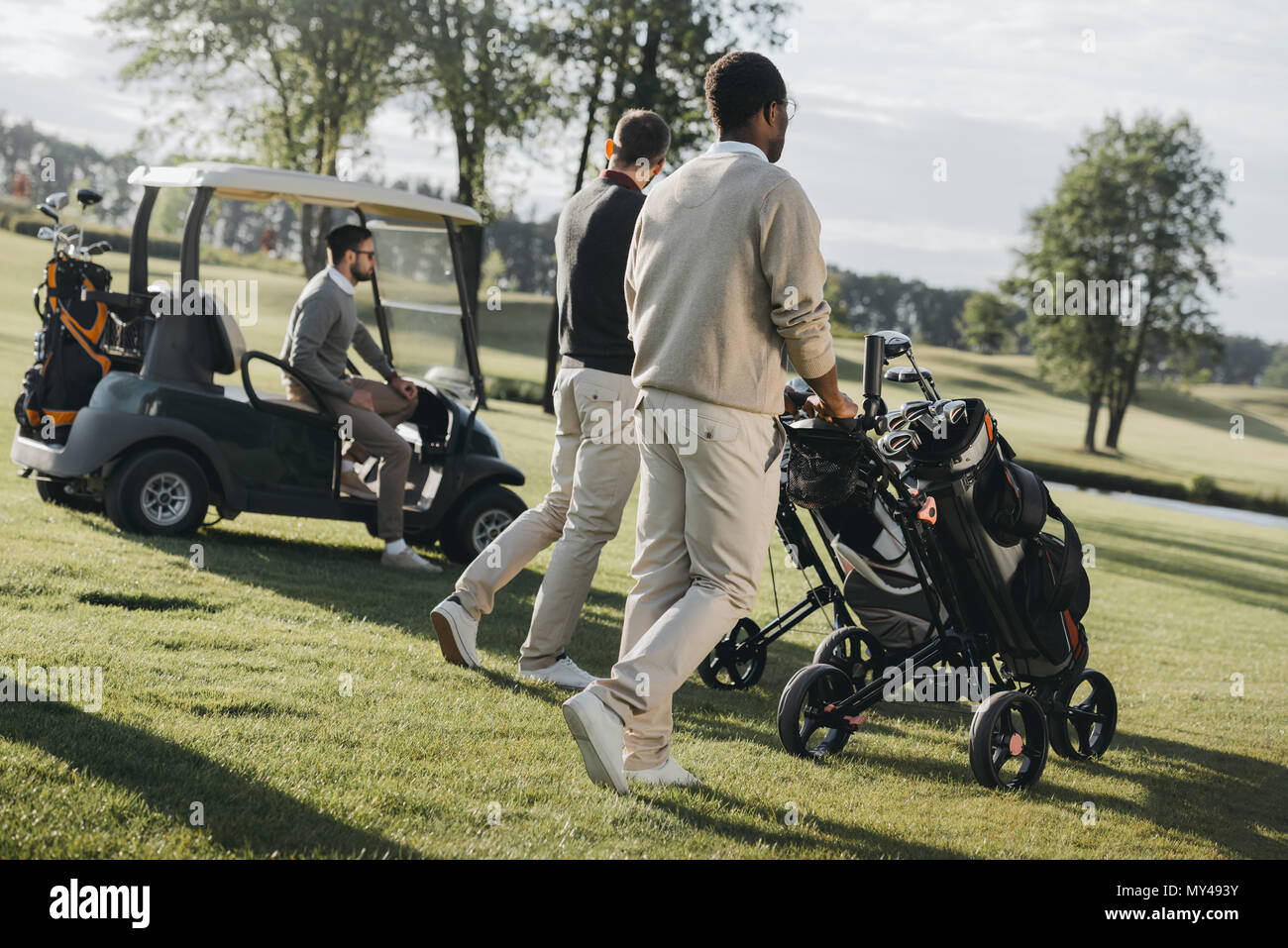 multiethnic golf players with golf bags and golf cart spending time together - Stock Image