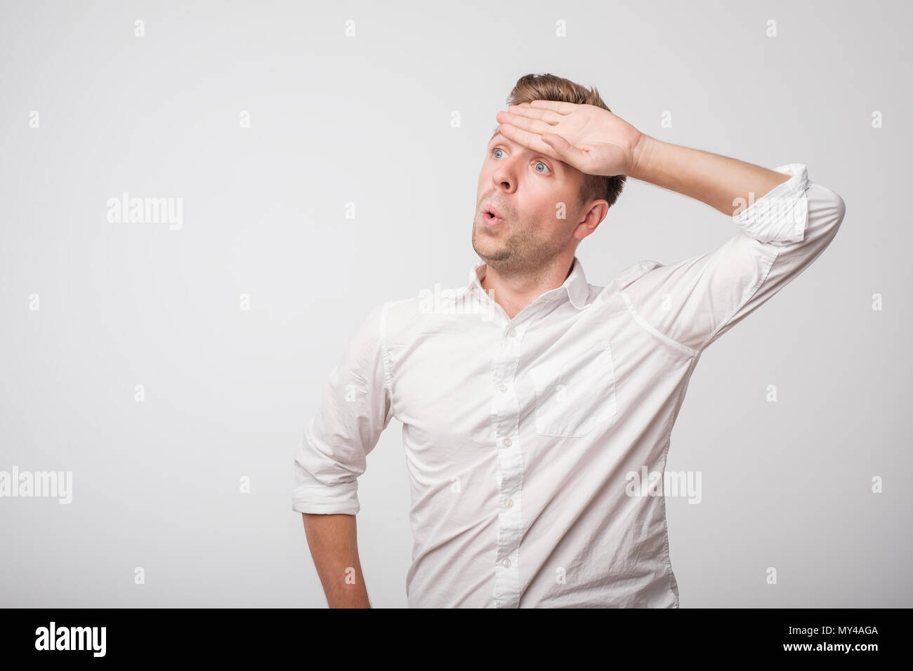 Tired caucasian man in white shirt sweating having fever headache - Stock Image
