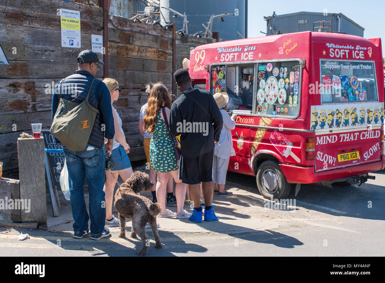 People queueing for ice creams beside the industrial unit on Whitstable seafront, Kent, England, UK. - Stock Image