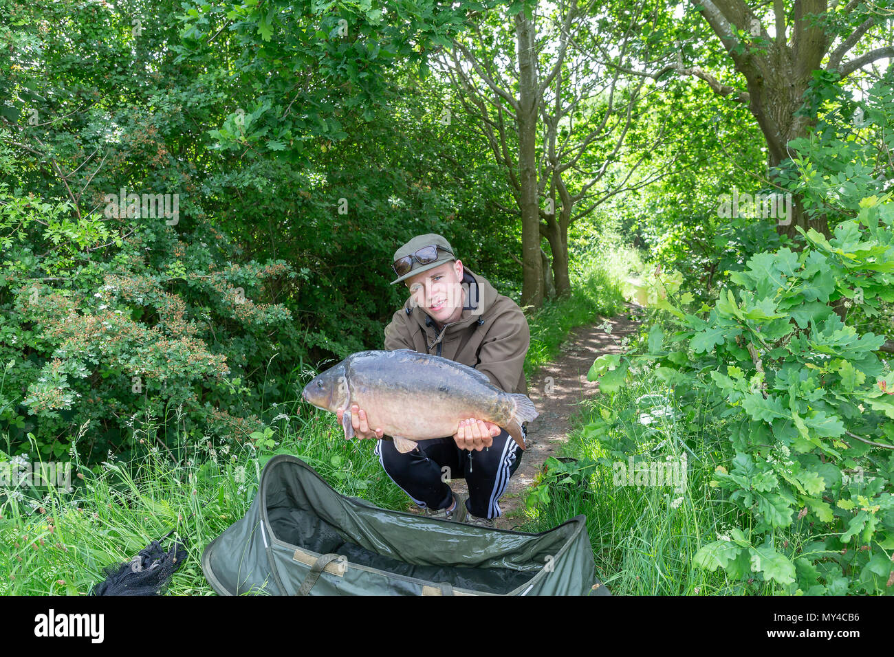 05 June 2018 - Young angler around Appleton Reservoir holds a 19 pound Carp with pride, Park Lane, Warrington, England, UK - Stock Image