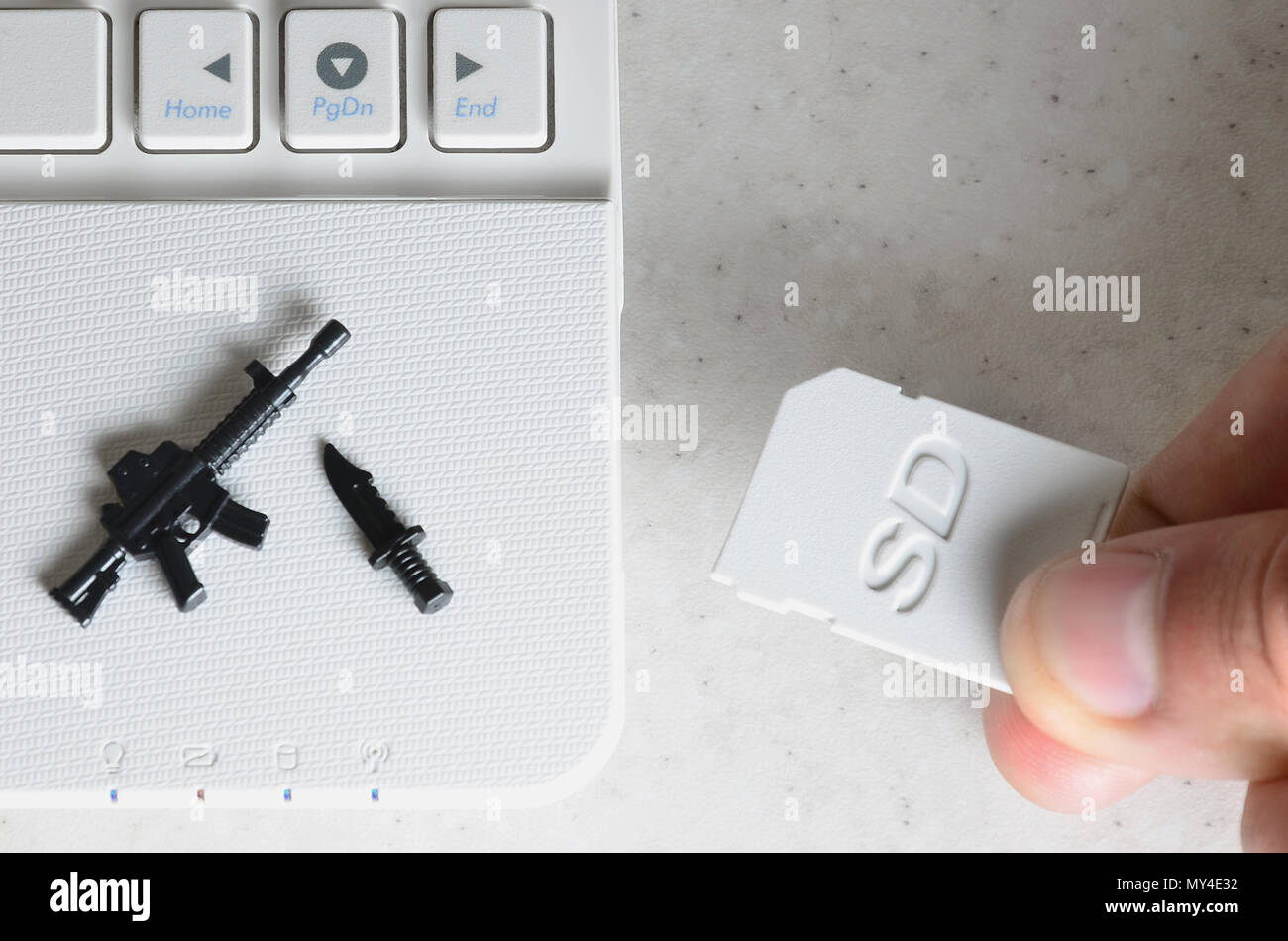 A hand inserts a compact SD card into the slot of a netbook, on which lie a miniature knife and gun. The concept of information warfare, journalistic  - Stock Image