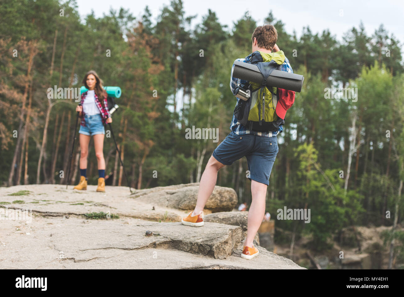 man taking photo of girlfriend with hiking equipment in forest - Stock Image