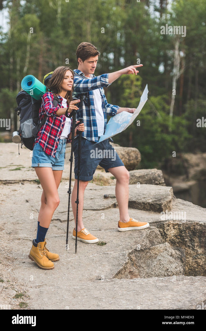 young couple of hikers with map on nature and pointing somewhere - Stock Image