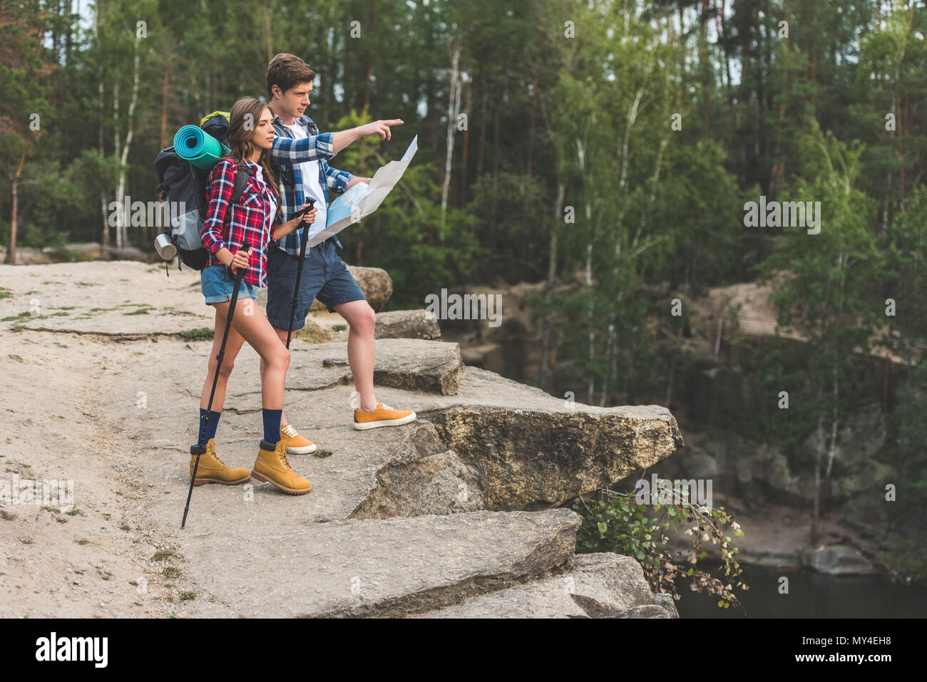 young couple of hikers with map on nature - Stock Image