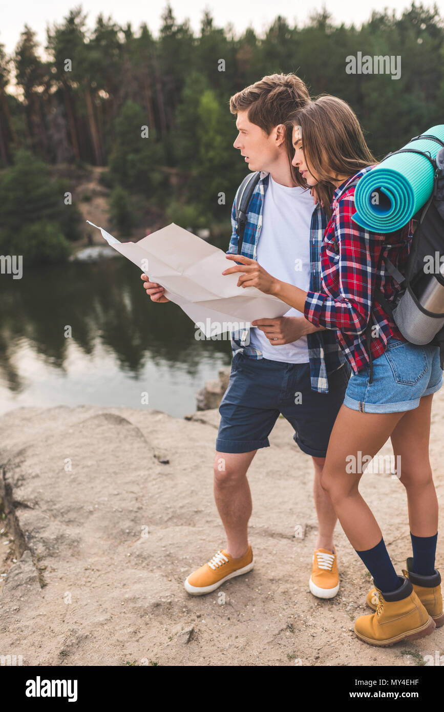 thoughtful young couple of hikers with map on nature - Stock Image