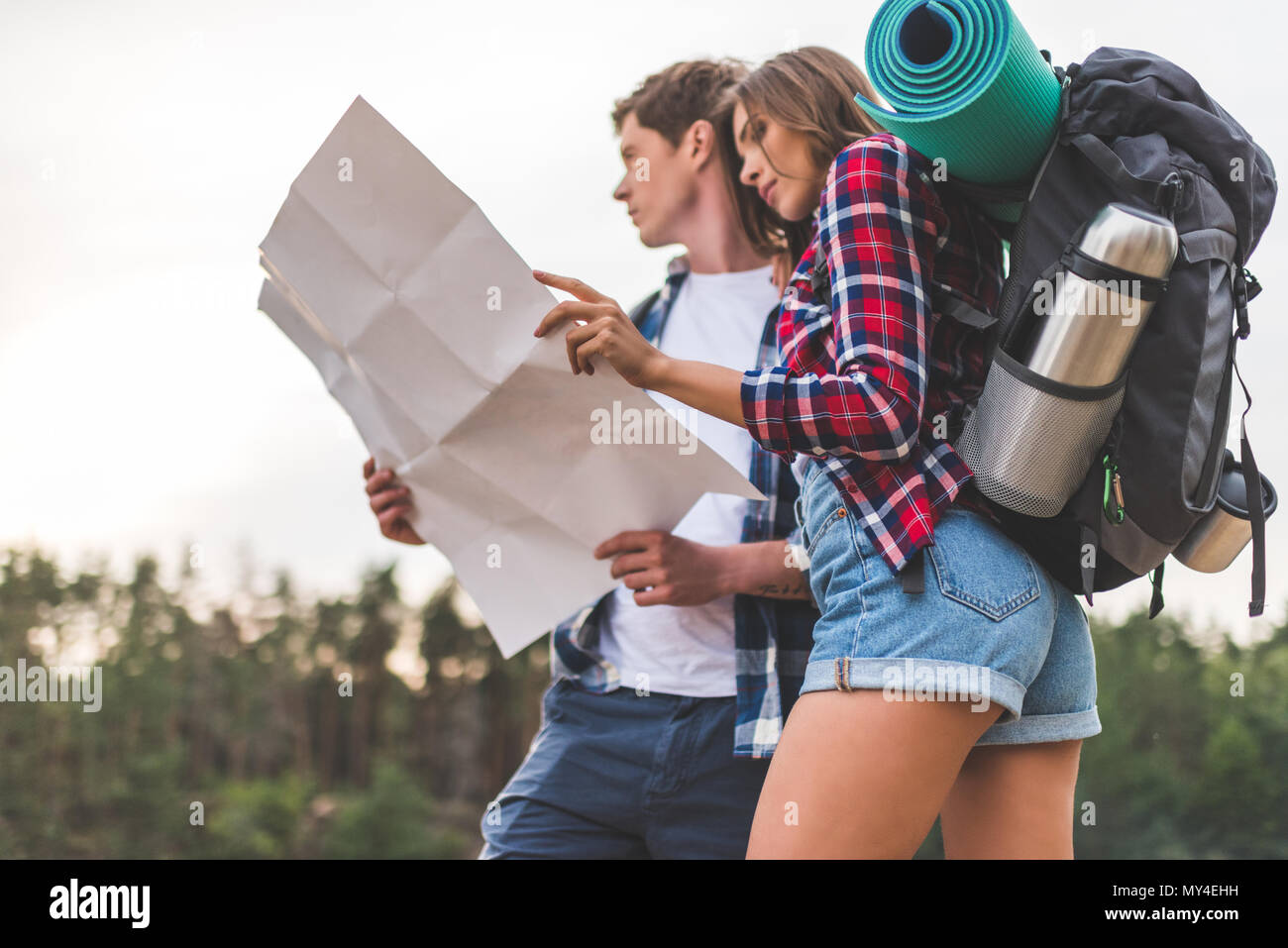 beautiful young couple of hikers with map on nature - Stock Image