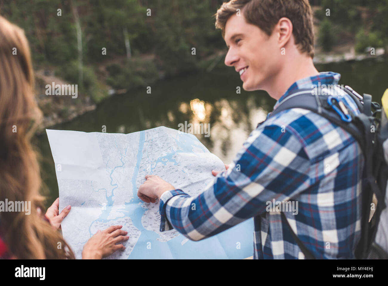 handsome young hiker showing his girlfriend point on map - Stock Image