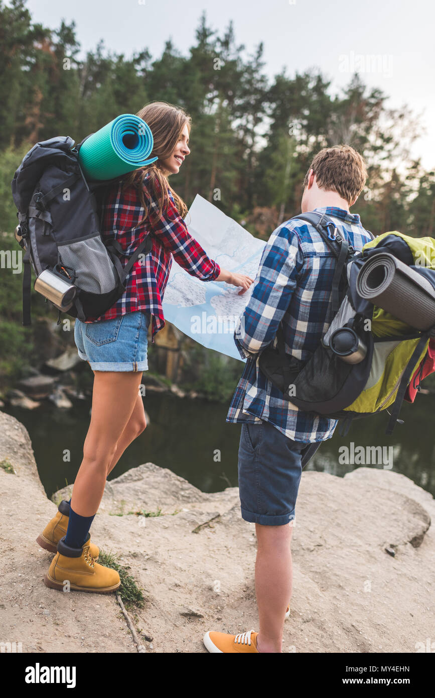 active couple with backpacks looking at map near mountain lake - Stock Image
