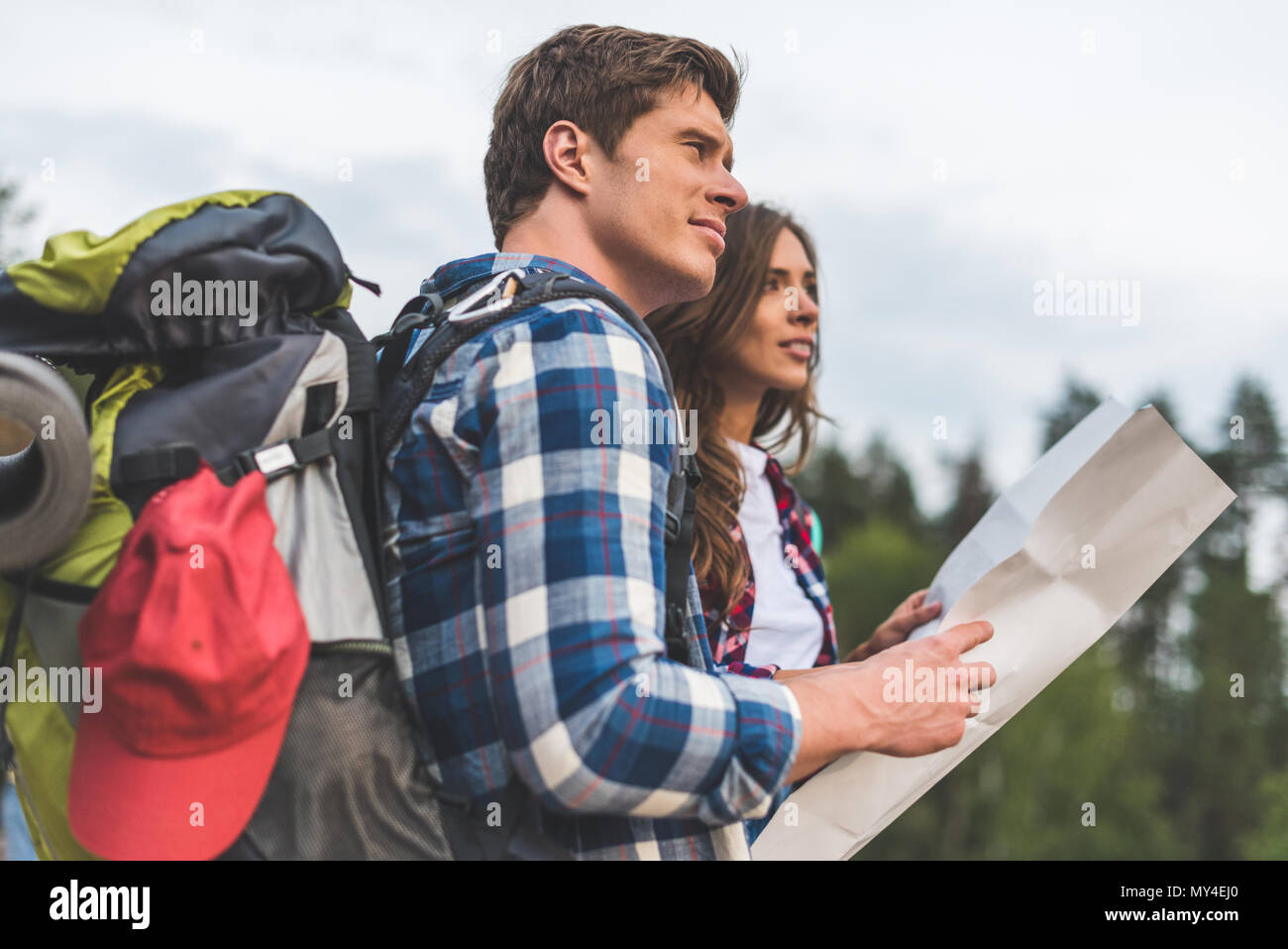 thoughtful active couple of hikers with map looking away - Stock Image