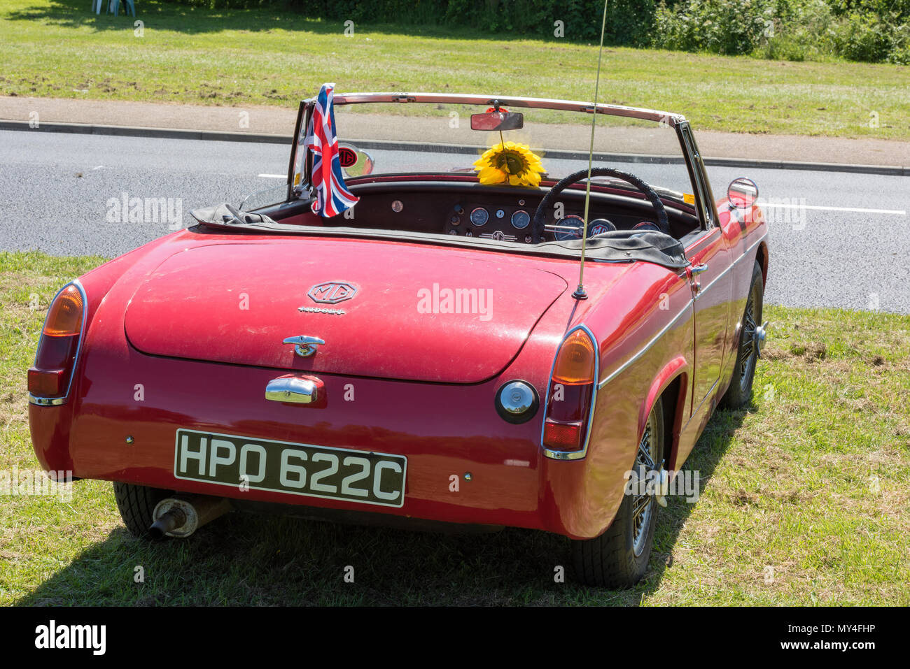 a vintage MG motor car or sports car with a sunflower on the dashboard and the roof down in the hot summer weather. MG midget vintage sports car. - Stock Image