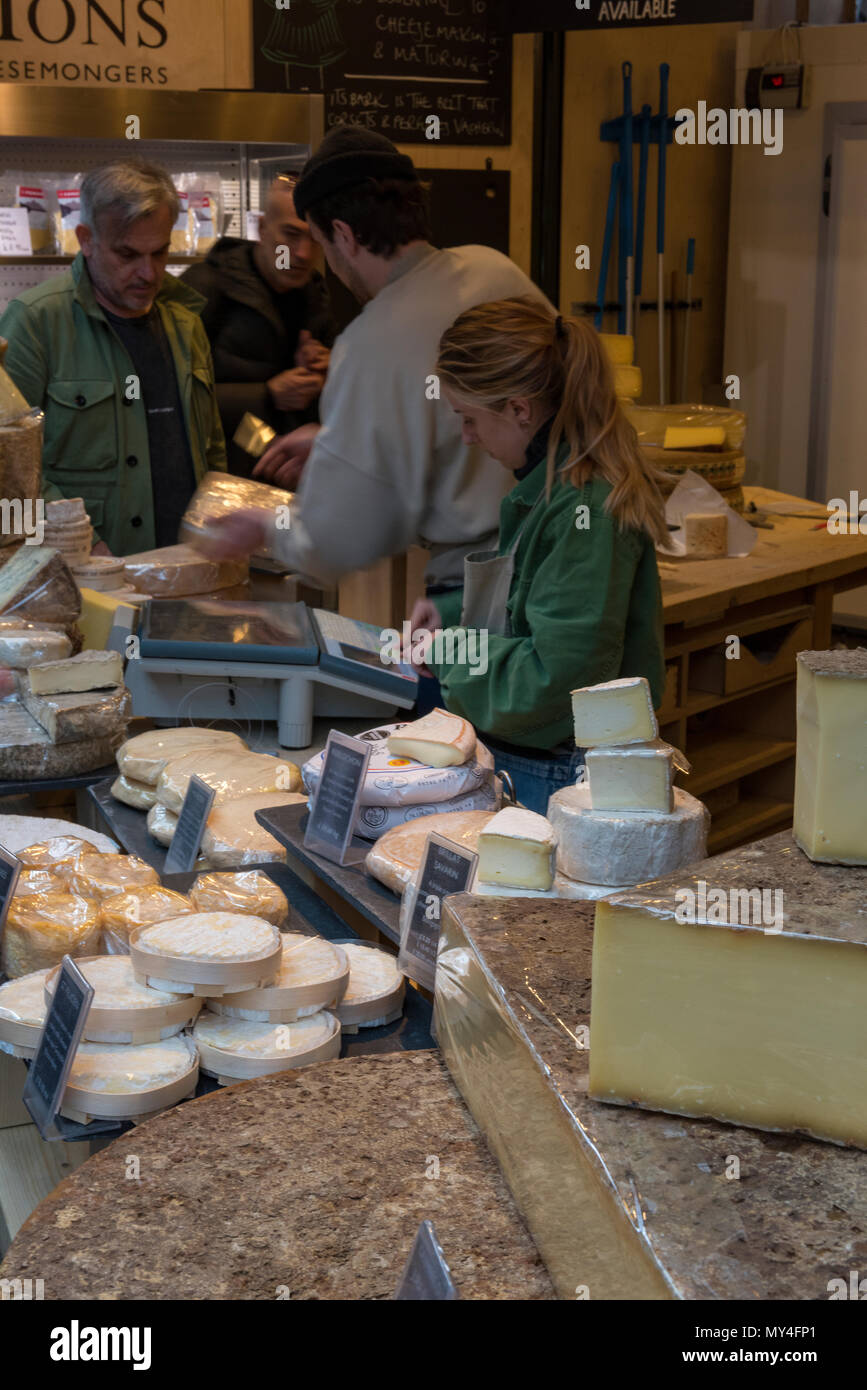 A woman on a cheese counter to market stall at borough market in central london. Serving on a stall selling dairy products on a marketplace stall. Stock Photo