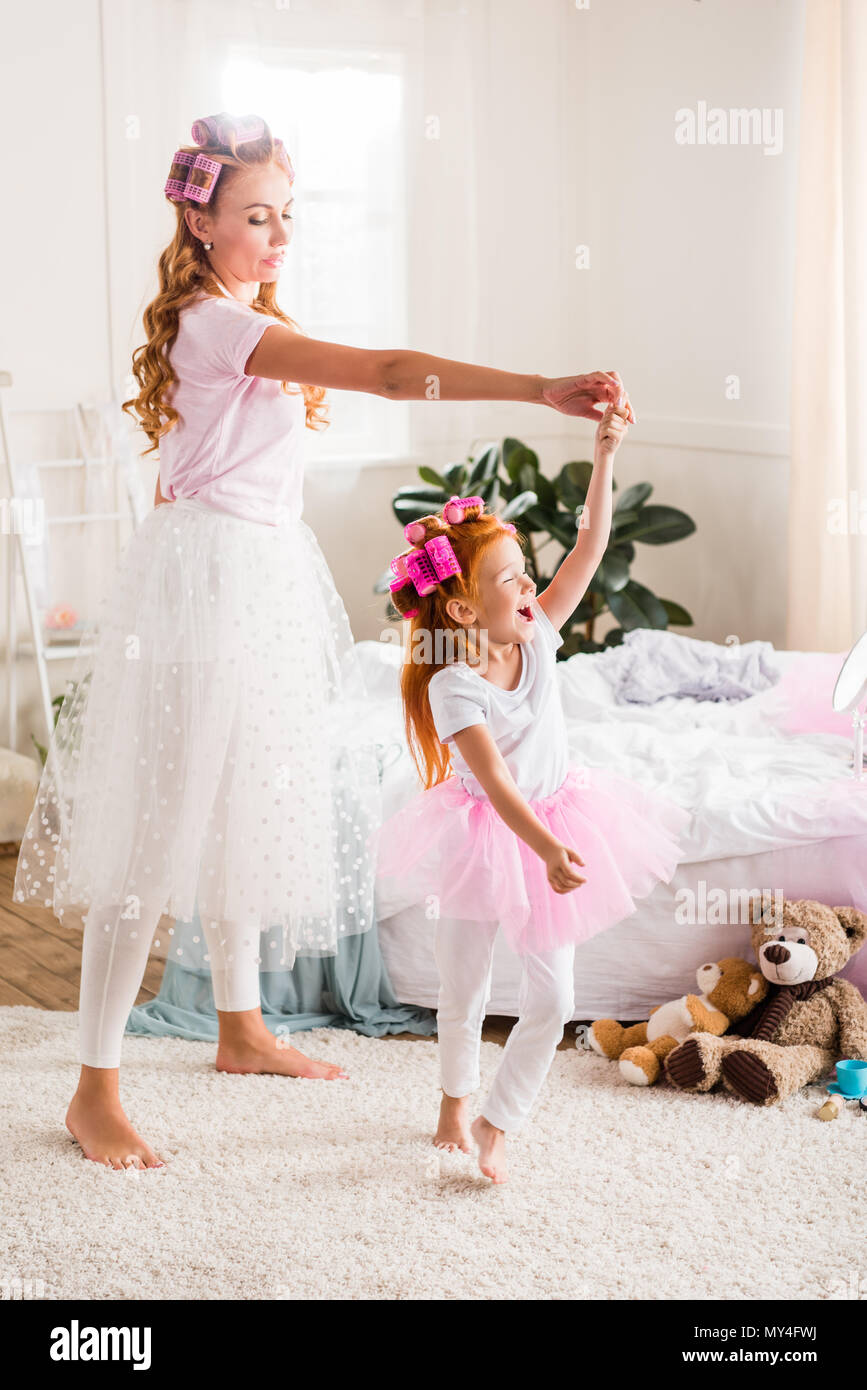 mother and daughter in tutu tulle skirts having fun together at home - Stock Image