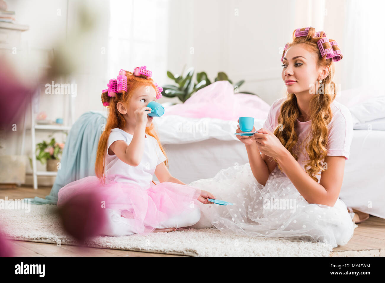 900eb554fc young mother and cute little daughter with curlers in tutu tulle skirts  having tea party together