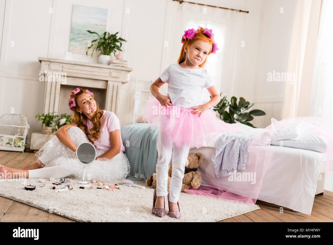023d6f8c00 little girl wearing curlers, tutu tulle skirt and mothers high heels at home  - Stock