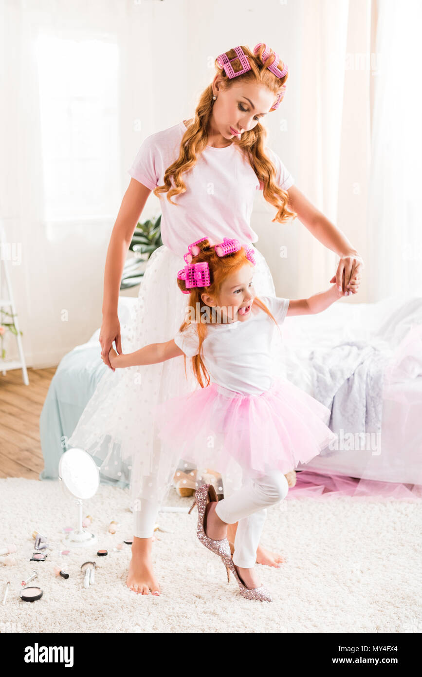 61cbdff0f0 mother and daughter in tutu tulle skirts holding hands while spending time  together at home -