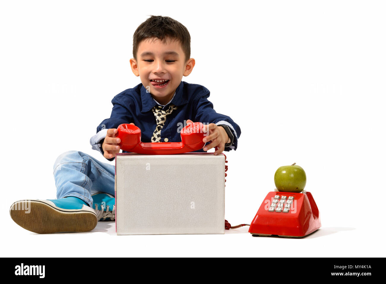 Studio shot of cute happy boy smiling while playing with old tel - Stock Image