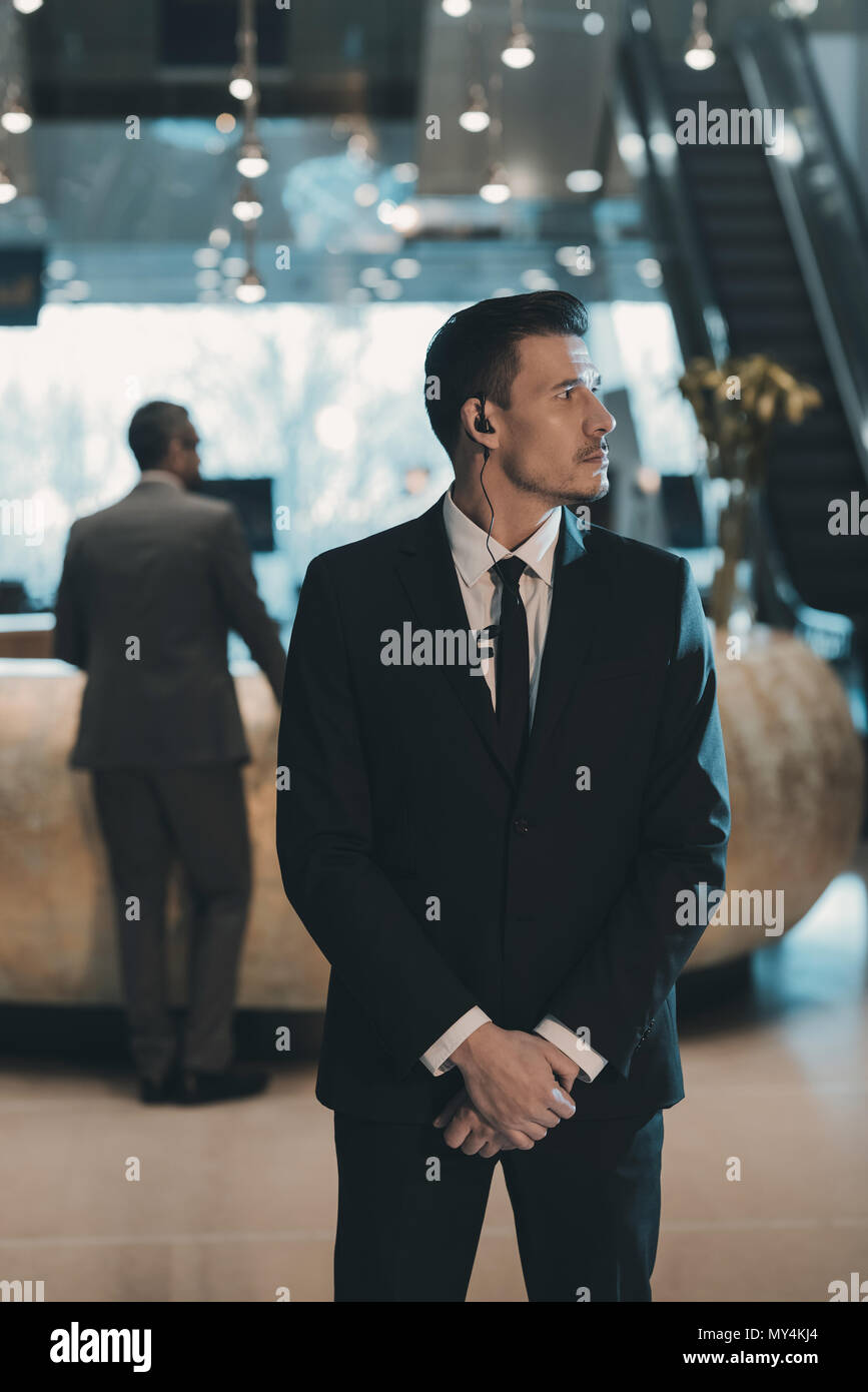 handsome bodyguard waiting for businessman at business center - Stock Image