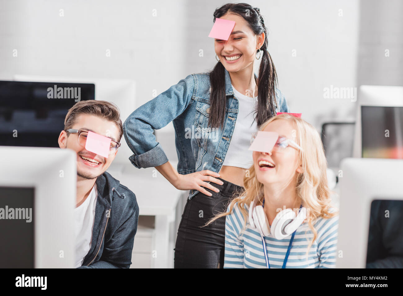 happy people with stickers on heads at modern office - Stock Image