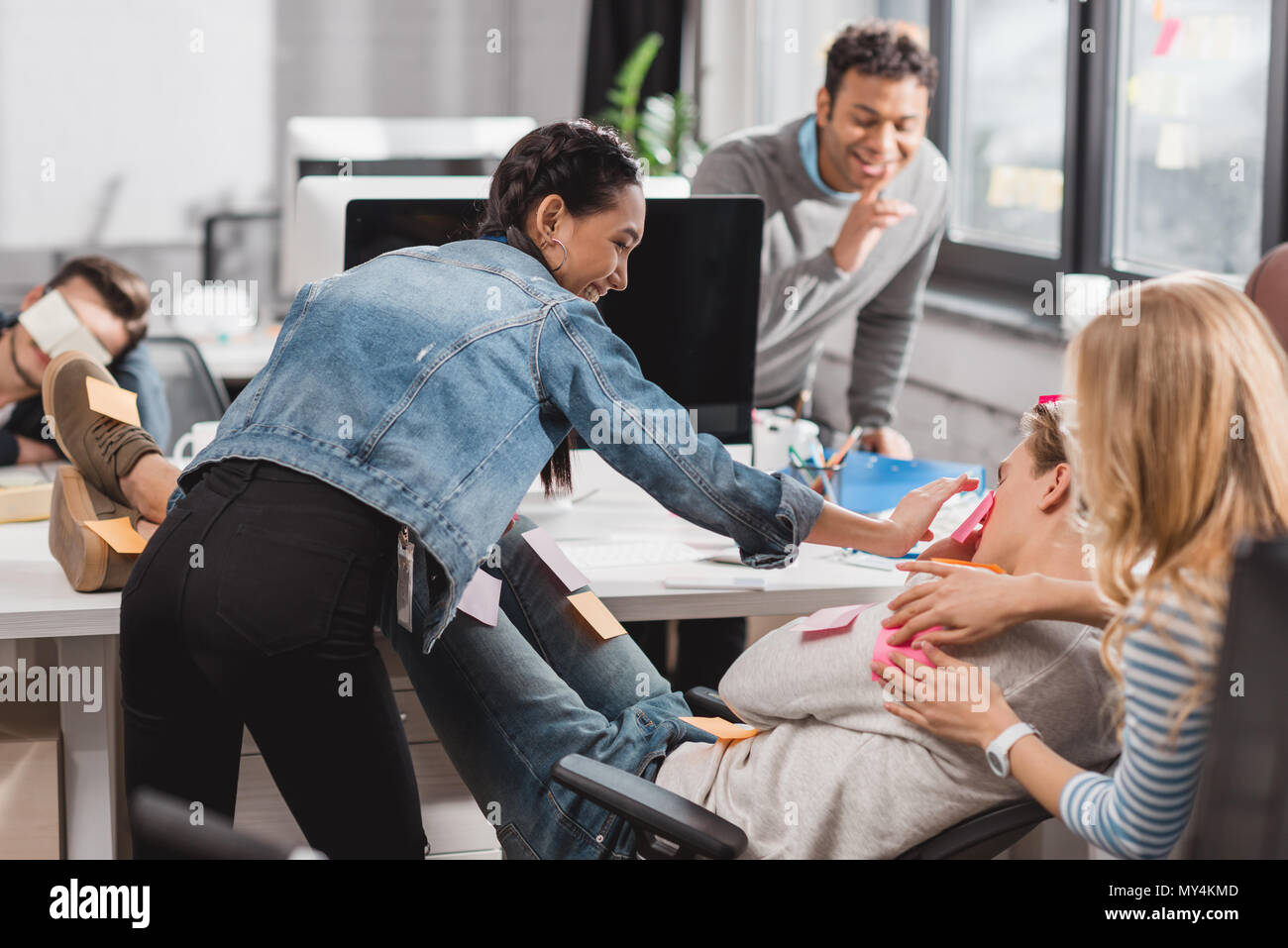 people having fun in office, women glue stickers on man - Stock Image