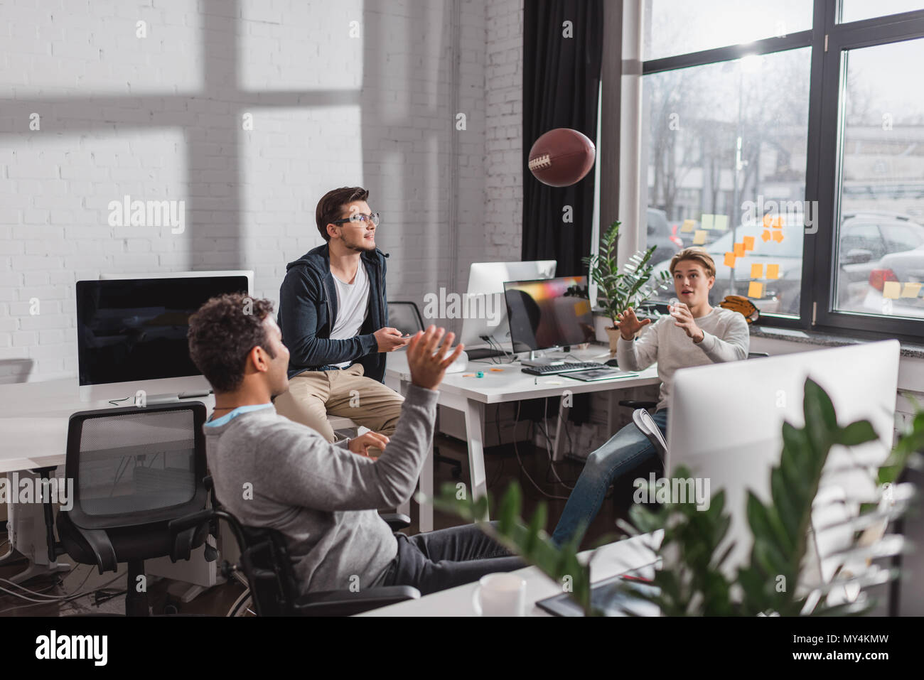 Men playing with ball in modern office - Stock Image