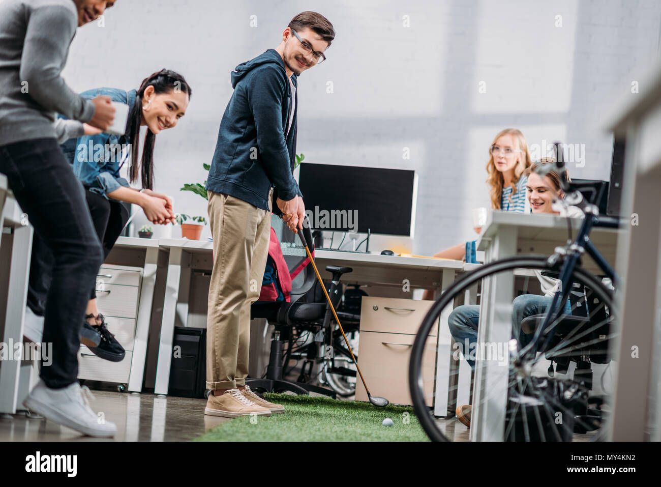 Workers Having Fun In Office Man Playing Mini Golf Stock