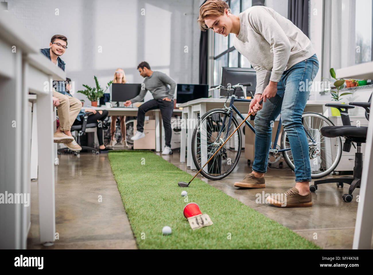 happy people playing in mini golf at modern office - Stock Image