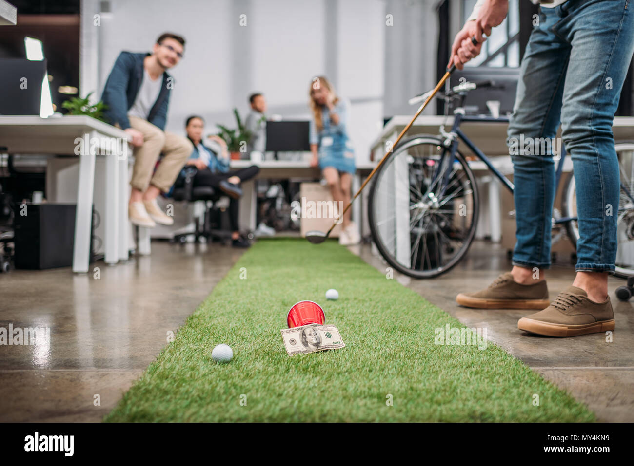 cropped image of people playing in mini golf at modern office - Stock Image