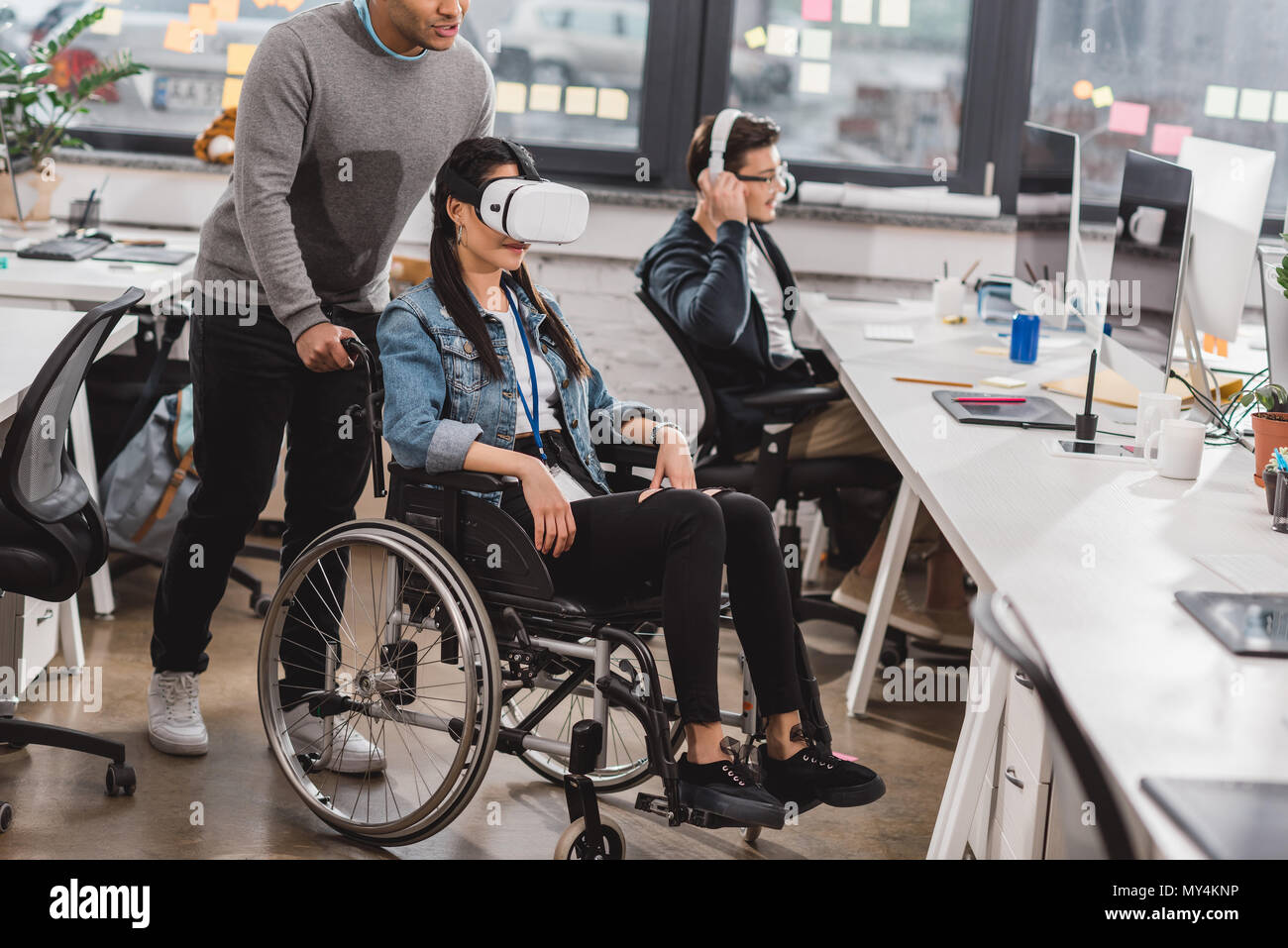 woman in wheelchair using virtual reality glasses at modern office - Stock Image