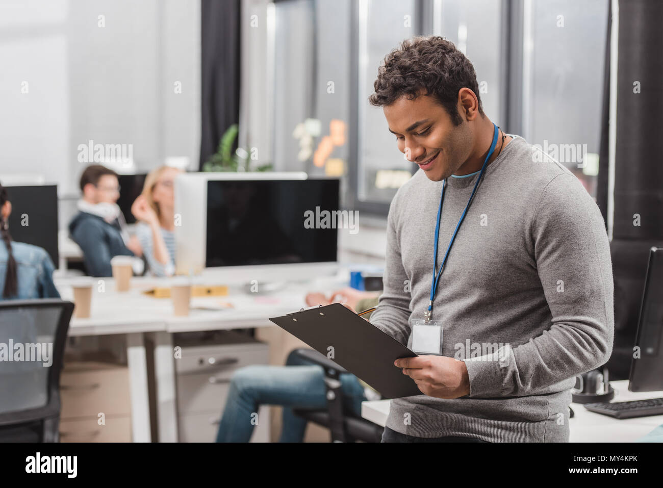 happy african american man with name tag writing something on planchette at modern office - Stock Image