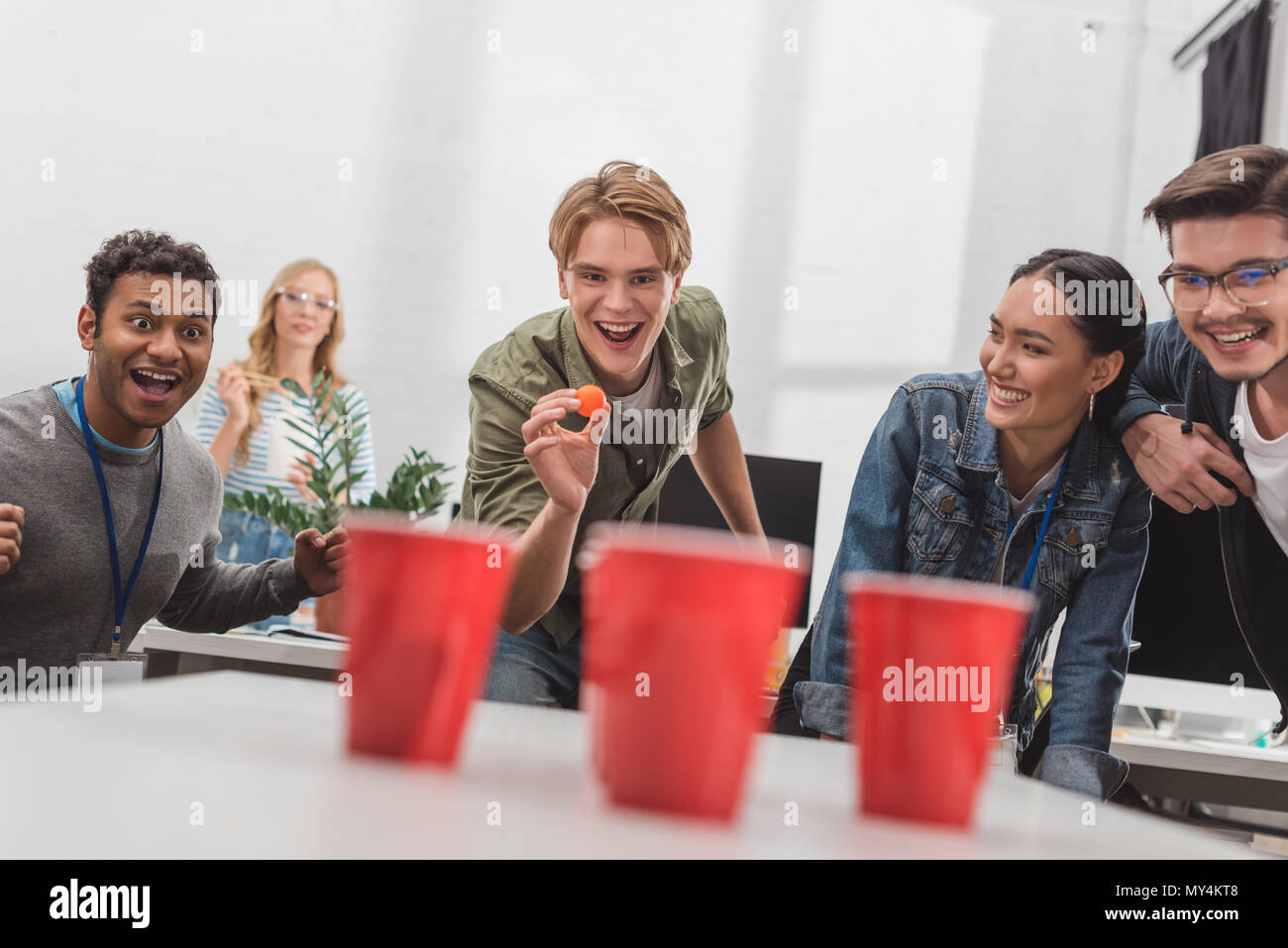 young attractive people playing beer pong at modern office after work - Stock Image