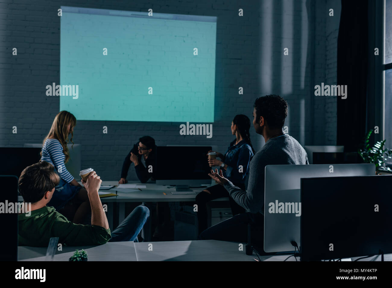 people watching presentation in office at nighttime. blank screen - Stock Image