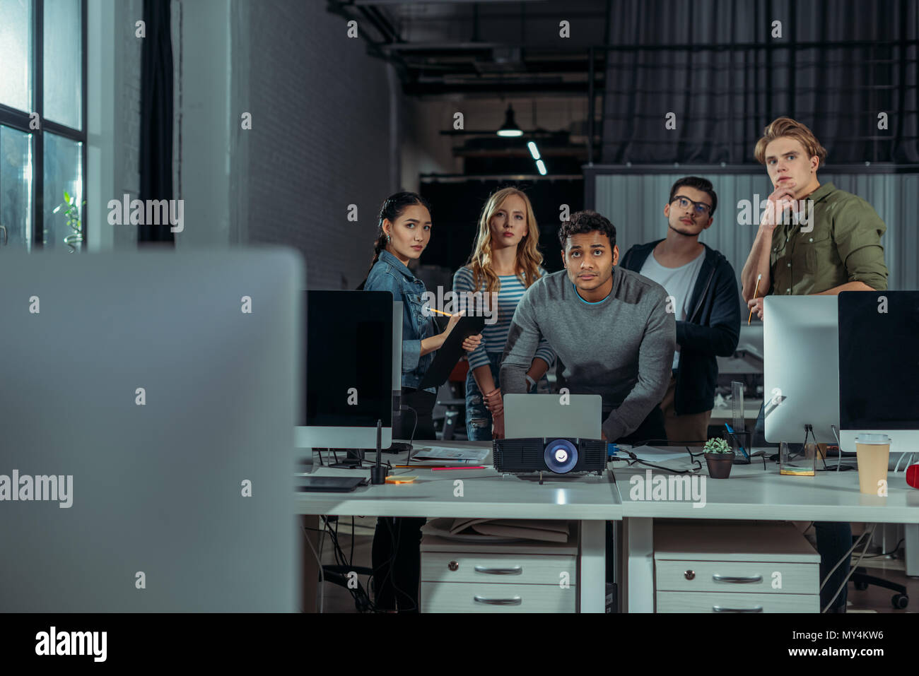 young people watching presentation in modern office at nighttime - Stock Image