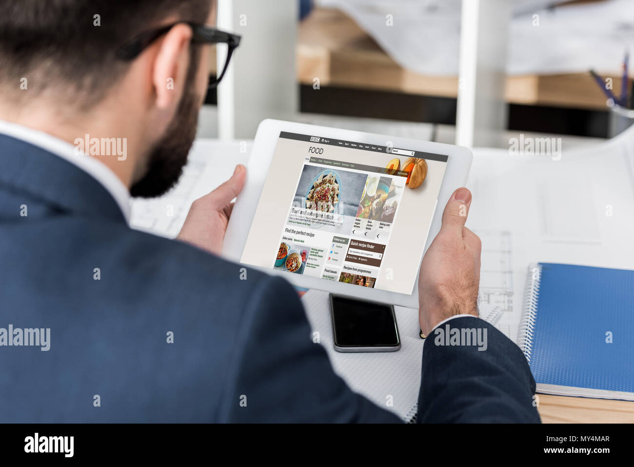 Businessman holding tablet with loaded bbc food page stock photo businessman holding tablet with loaded bbc food page forumfinder Image collections