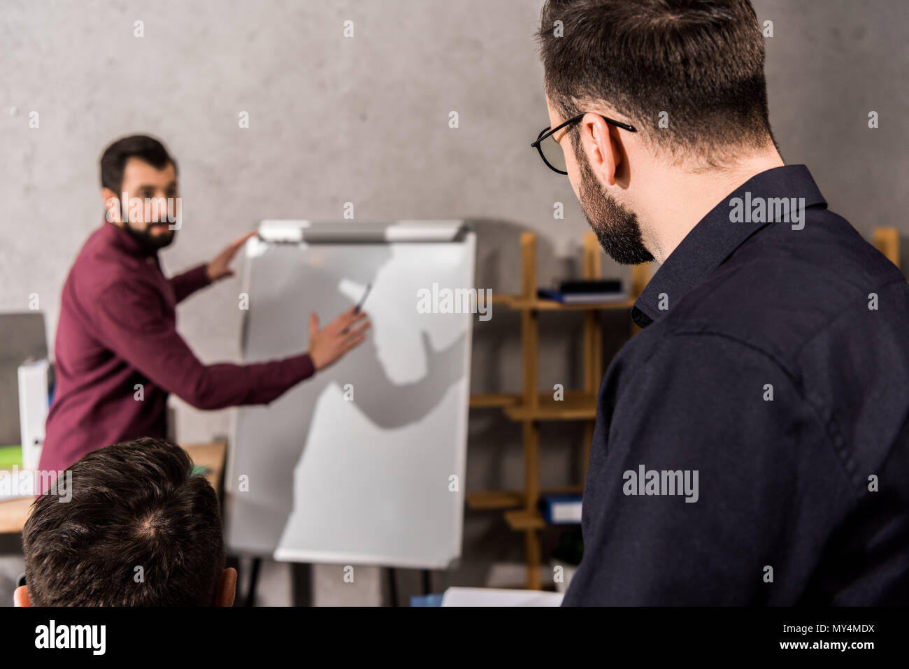 businessman describing something to colleagues at flipchart in office - Stock Image