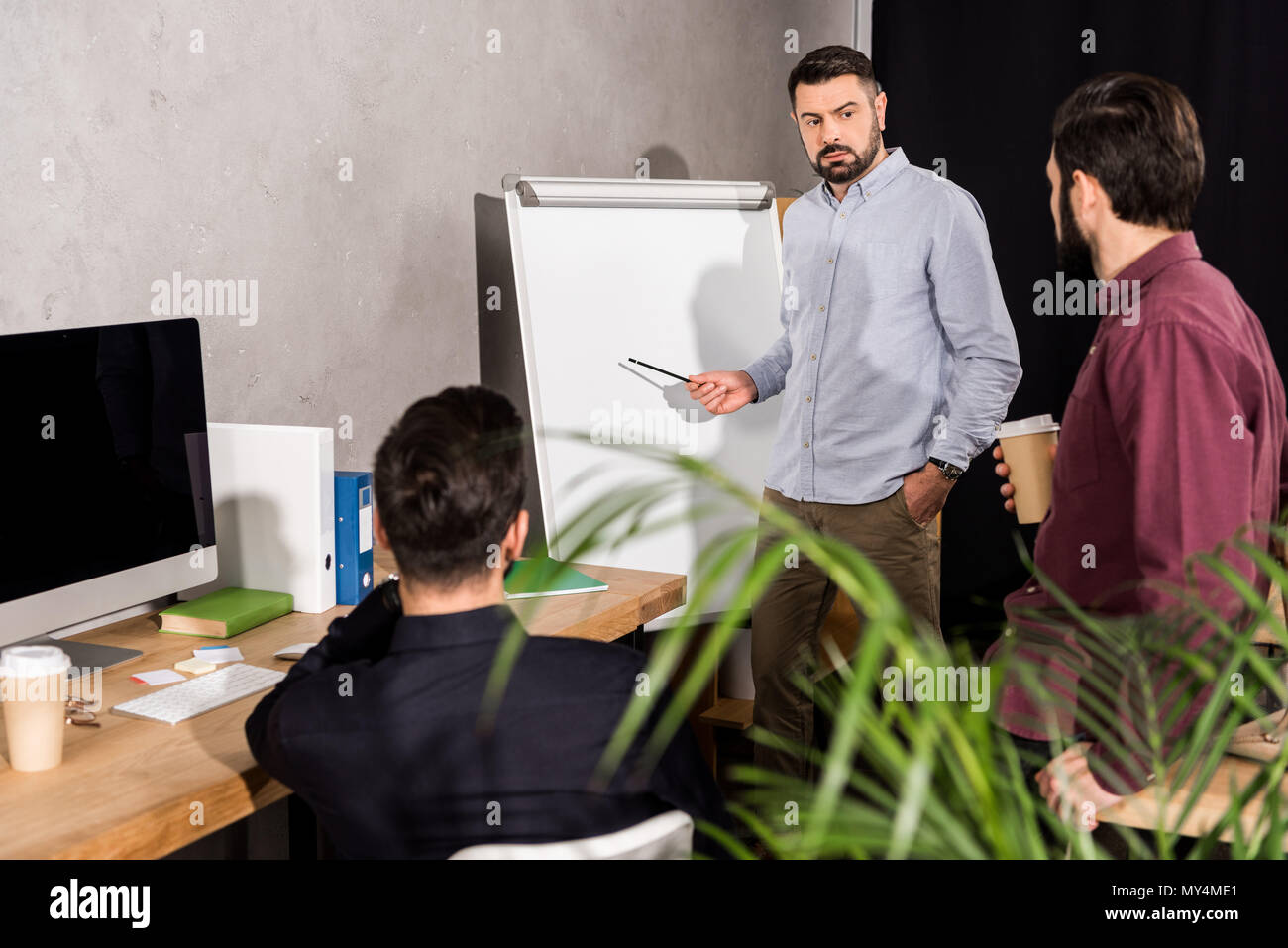 businessman describing something to colleagues at meeting in office - Stock Image