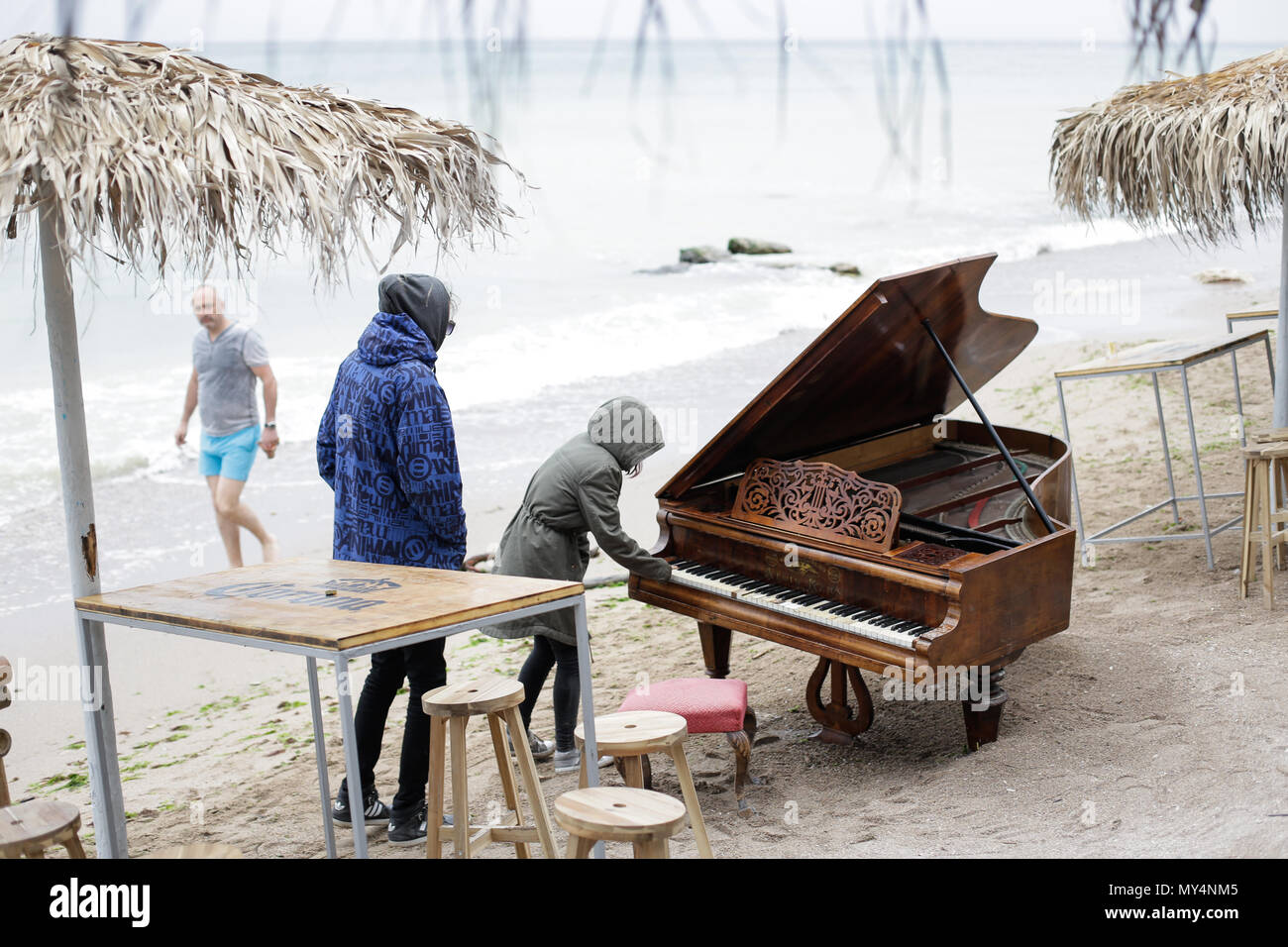 VAMA VECHE, ROMANIA - MAY 1, 2018: Young people playing with an old piano, after partying all night, early in the morning just before sunrise in the s - Stock Image