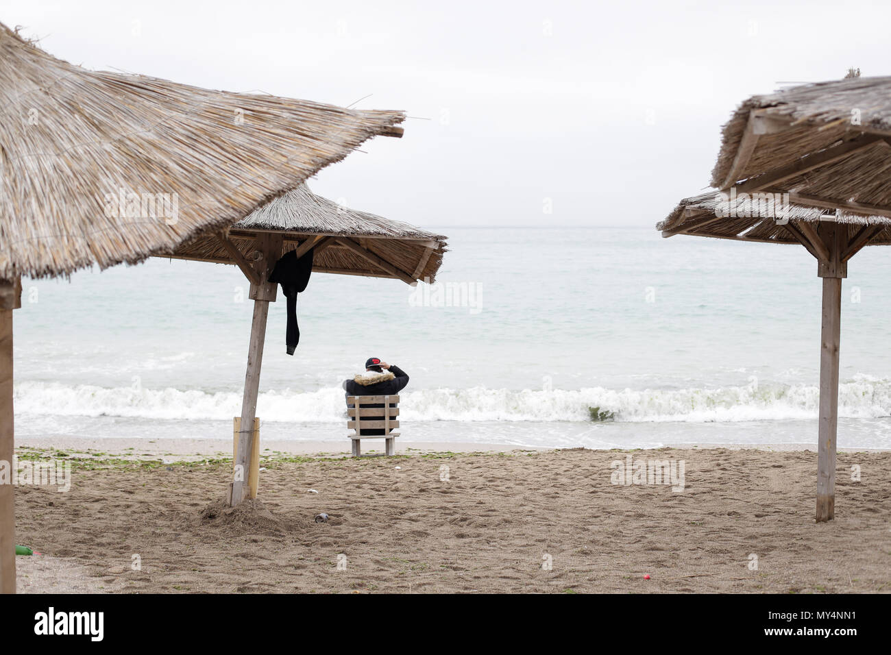Young man relaxing on the beach after partying all night, early in the morning just before sunrise in the seaside resort of Vama Veche, Romania - Stock Image