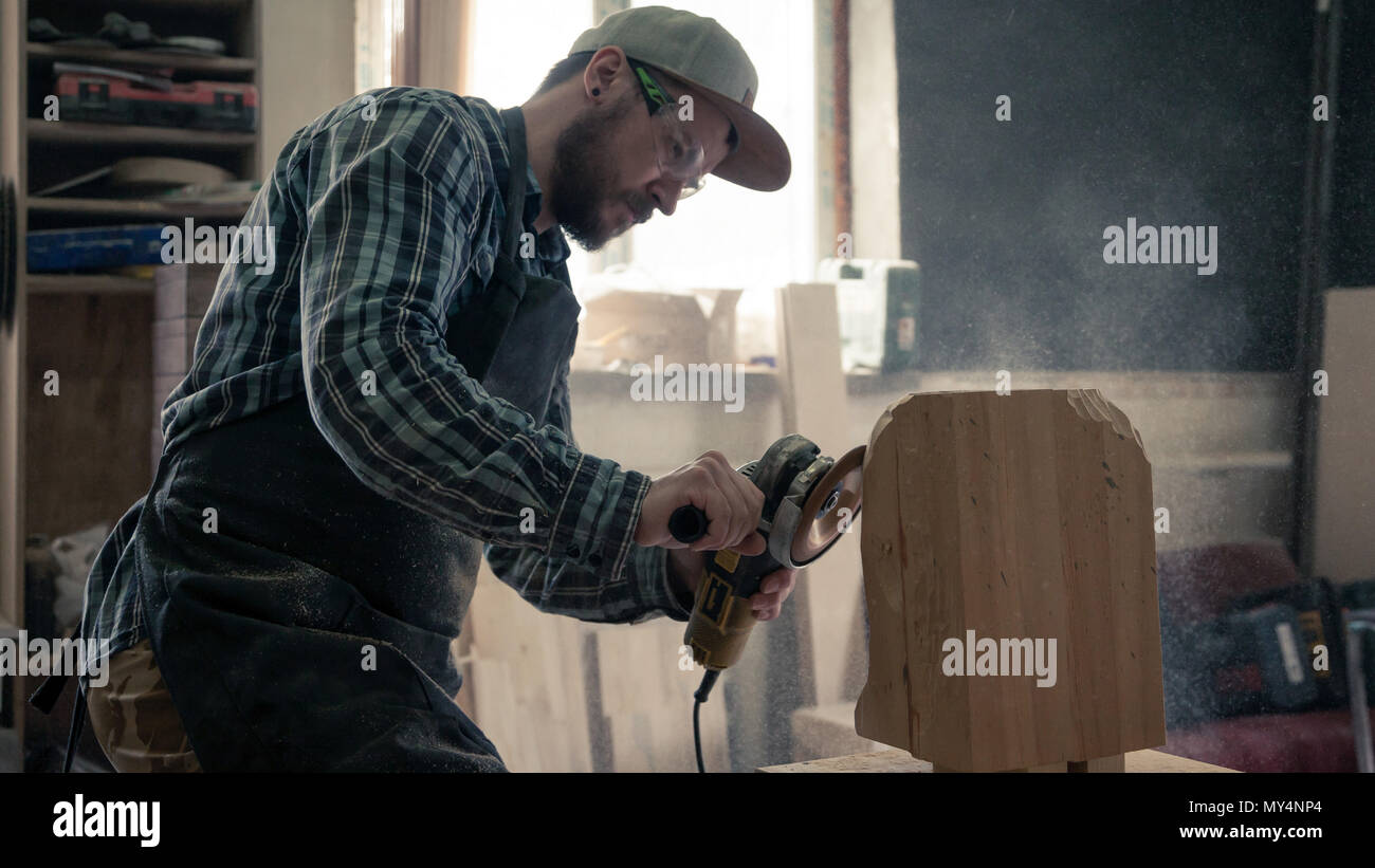 Сarpenter in work clothes and small buiness owner working in woodwork workshop, processes the board with an angle grinder , on the table is a hammer a - Stock Image
