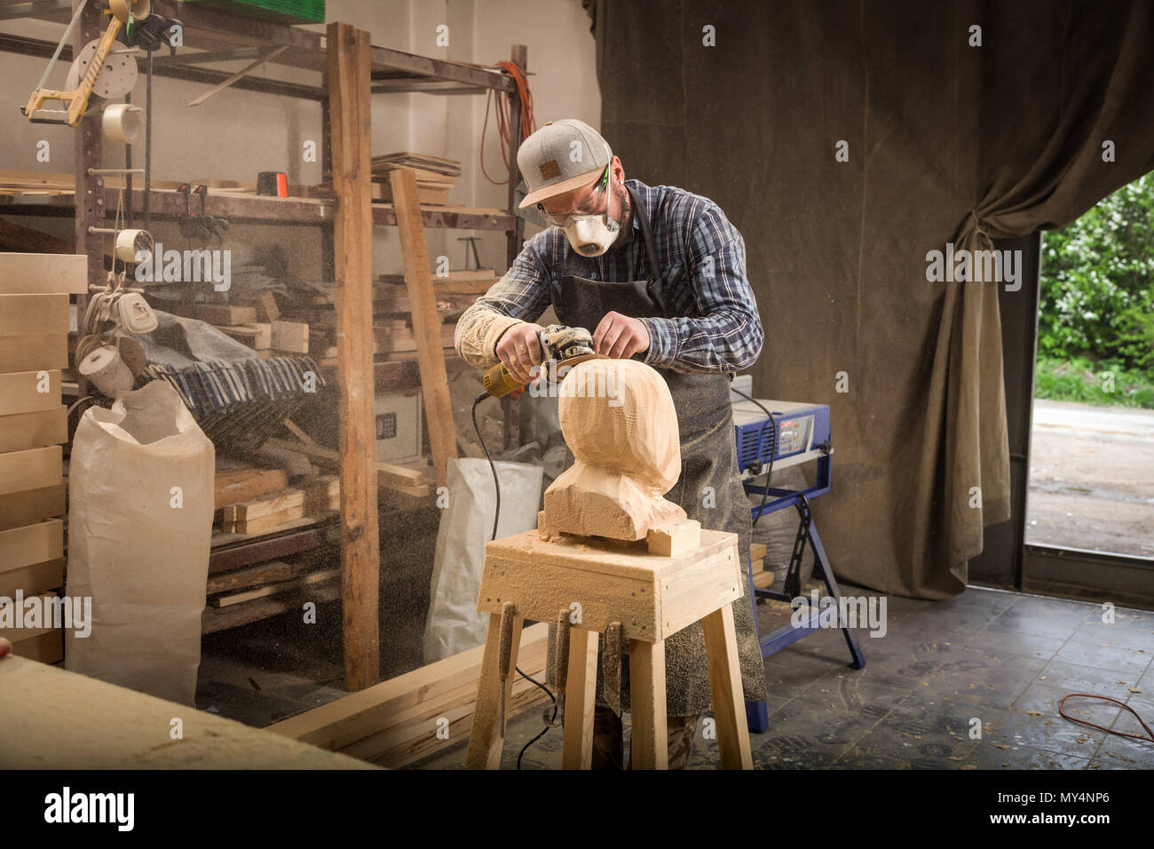 Close up  young man carpenter in a suit, goggles   saws a man's head with a tree , using an angle grinder  in the workshop, around a lot of tools for  - Stock Image