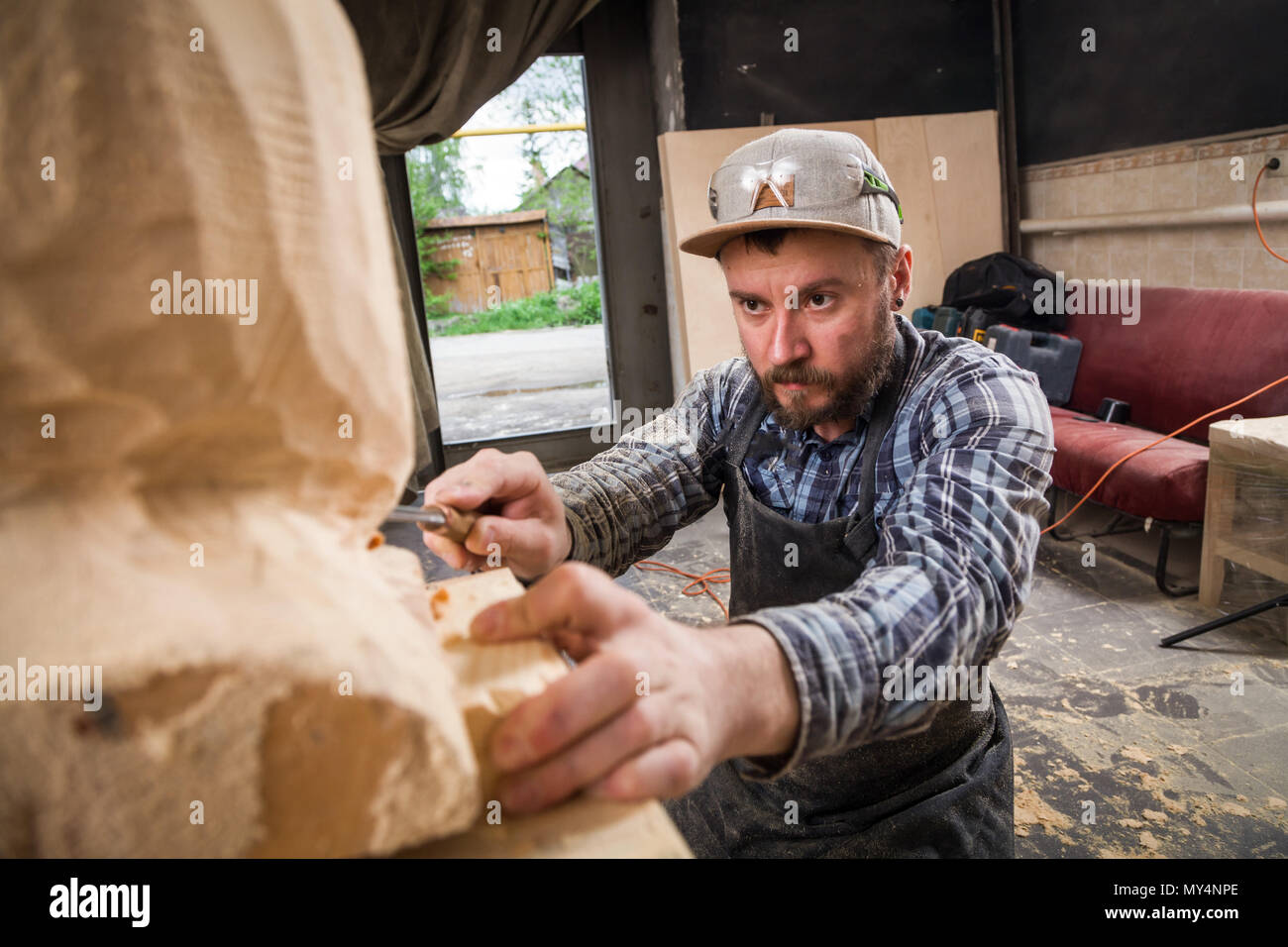 Young man carpenter in a work clothes  saws a man's head with a tree , using a chisel  in the workshop, around a lot of tools for work - Stock Image